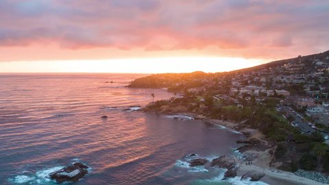4K aerial sunset time-lapse footage over the ocean shot from the drone in Laguna Beach in California showing coastal homes, beach houses, mountains and the Pacific ocean waves.