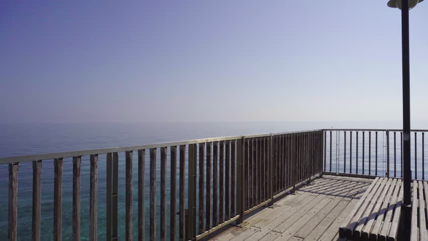 Happy girl runs to pier hand-rail, rise hands in the air and smiles. Camera follows the woman   Shutterstock HD Video #27960571