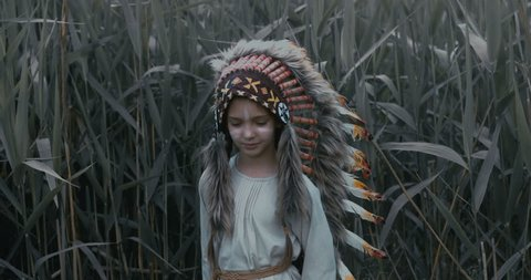 Little girl playing outdoors, wearing Indian headdress, pretending to be a native American. Walking and looking into camera