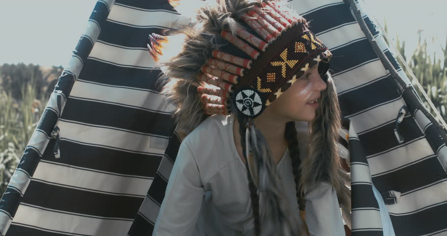 Little girl playing in a teepee tent outdoors, wearing Indian headdress, pretending to be a native American. 4K UHD RAW edited footage | Shutterstock HD Video #27964381