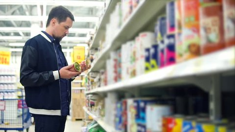 Man in the supermarket shopping in the section of pet supplies, he comparing two food cans