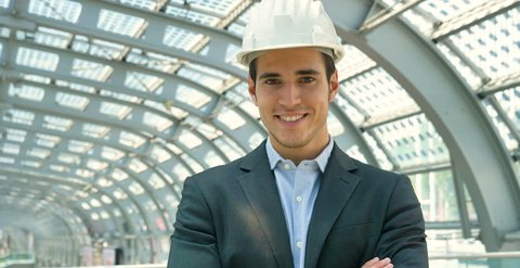 A young handsome, engineer, foreman, architect (builder) looks at the construction of the structure, at the station, wearing a white protective helmet, smiling in a suit. Concept: good work, project.