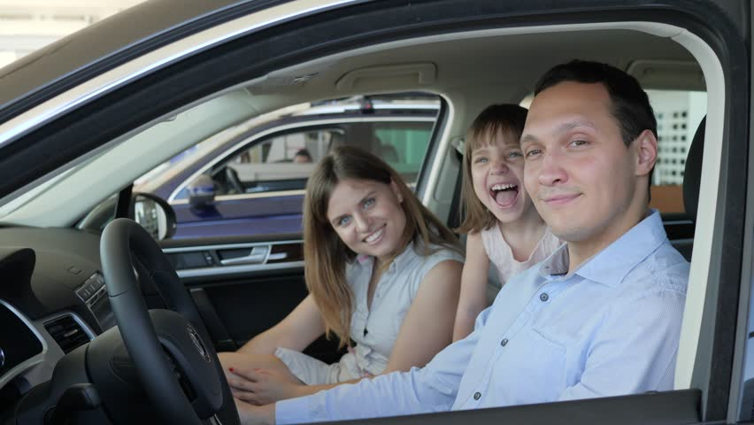 family in car center, joy of buying automobile, portrait of happy people sitting in new vehicle