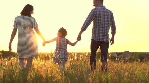 Happy Young Family with child walking on summer field. Healthy mother, father and little daughter girl enjoying nature together, outdoors. Sunset. Slow motion. 4K UHD video 3840X2160