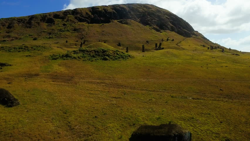 WS AERIAL Moai statues in green hills by sea / Tapati Rapa Nui, Easter Island, Chile