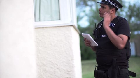 An Asian policeman asks questions to a member of the public on a doorstep, writing notes to help him find clues to solve a crime report. Police working together with the community.