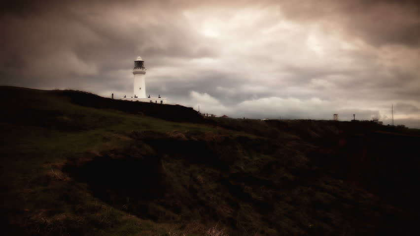Lighthouse daytime stock footage. A white Lighthouse set against a dramatic cloudy skyline.