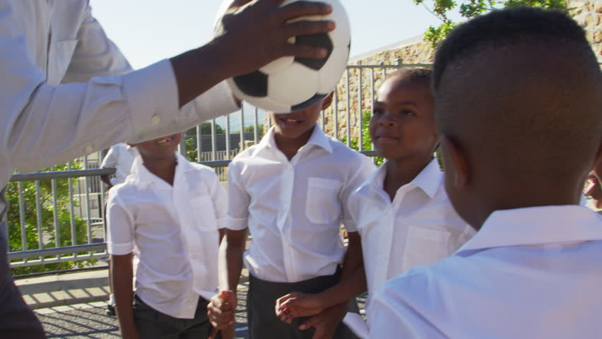 Teacher passes football to young kids in school playground
