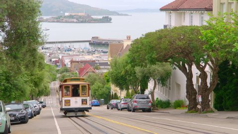 SAN FRANCISCO, CA - CIRCA APRIL 2017: San Francisco cable car trolly climbs up hill with Fisherman's Wharf and Alcatraz prison in background. 4K.