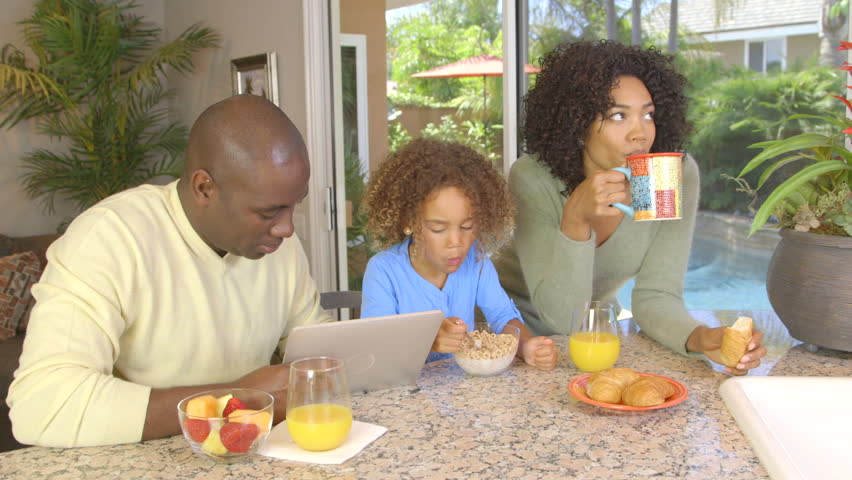 African American Family Eating Breakfast And Using Laptop