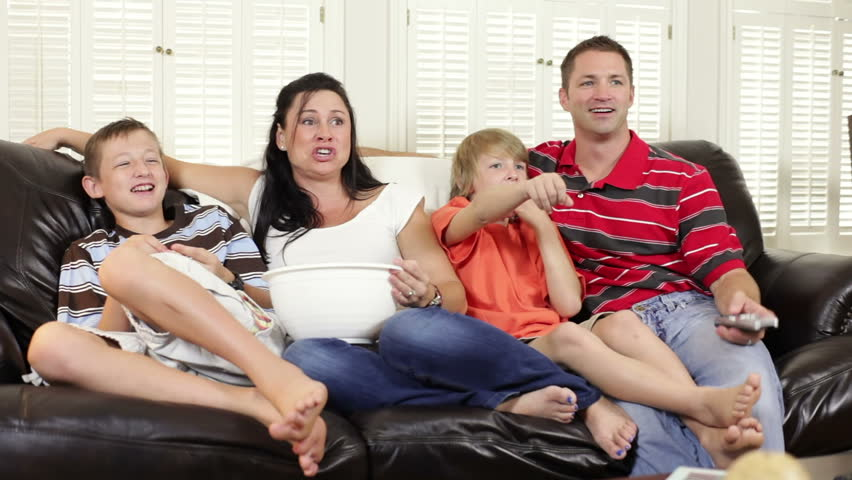 Mom and dad with their two boys sitting on a couch watch TV together. Camera dolly shot.