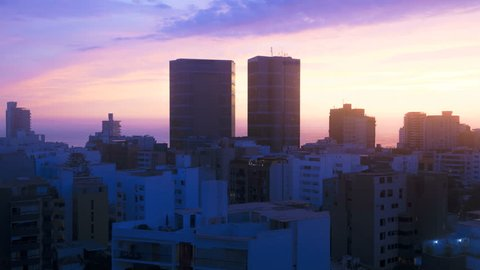 Day to night time lapse illuminated High rise cityscape view of Lima Peru Skyline a coastal Pacific Capital city South America