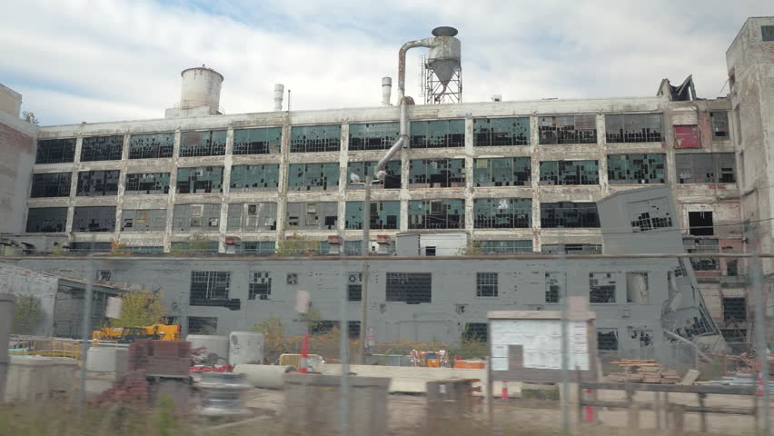 CLOSE UP: Driving past the construction site at the deserted crumbling Fisher Auto Body Plant in decaying Detroit, USA. The ruins of once famous car factory became a repository for building materials