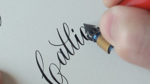 Calligrapher writing a word Calligraphy with point nib pen and black ink on white paper.