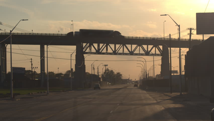 CLOSE UP, FPV: Semi trucks driving over the overpass, transporting goods across the busy multiple lane highway full of cars at golden sunrise in industrial city Detroit, America.