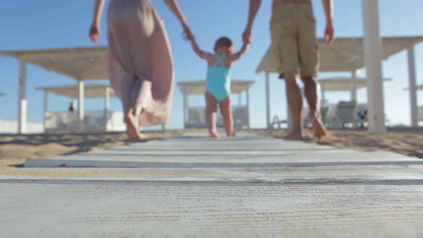 Happy family on the beach. Baby first steps.