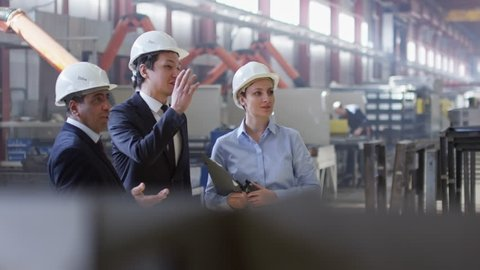 Slow motion shot of Asian and Latin-American engineers standing with female colleague in factory workshop,talking about something and then walking around.Woman holding documents and portable radio set