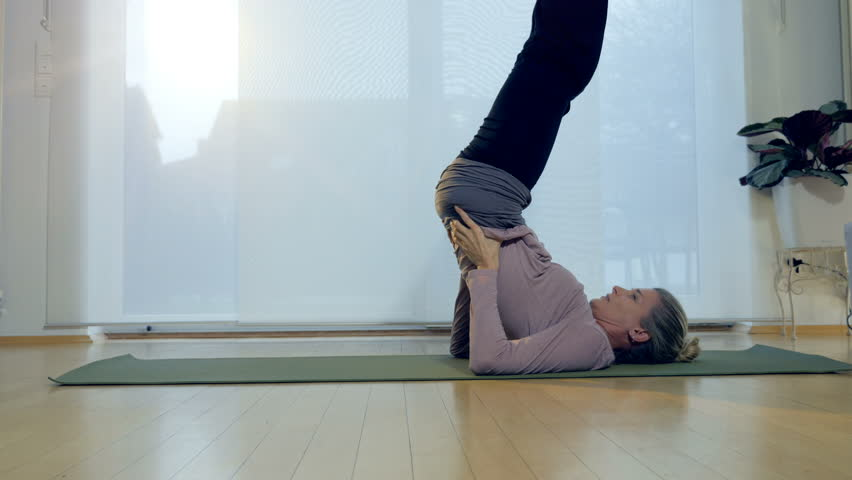 A woman performs the plow pose yoga position.   | Shutterstock HD Video #28158001