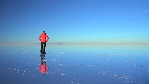 Tourist at sunset viewing the Bolivian Salar de Uyuni mineral Salt flats an Extreme Terrain Wilderness South America
