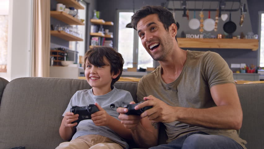 Father And Son Sitting On Sofa In Lounge Playing Video Game | Shutterstock HD Video #28172461