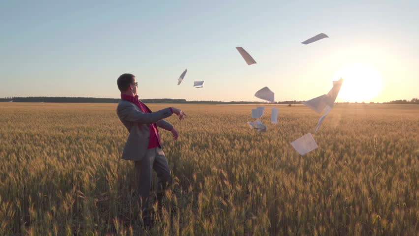 Businessman in a suit walks along the wheat field towards the sun, holds a pile of treaties in his hands and throws them out with a swing, slow motion