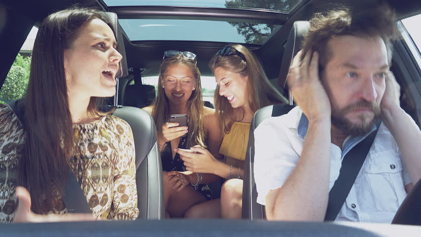 Teenage daughters laughing while parents are fighting in car unhappy