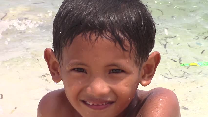 SULANGAN, PHILIPPINES - CIRCA MARCH 2017:  portrait of a Filipino kid that plays and baths on a beach on the ocean near the village of Sulangan, Eastern Samar, Philippines.