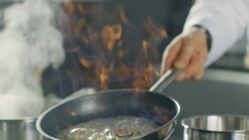 Close-up of a Chef Preparing Flambe Style Dish on a Pan. Oil and Alcohol Ignite with Open Flames.  Shot on RED EPIC-W 8K Helium Cinema Camera.