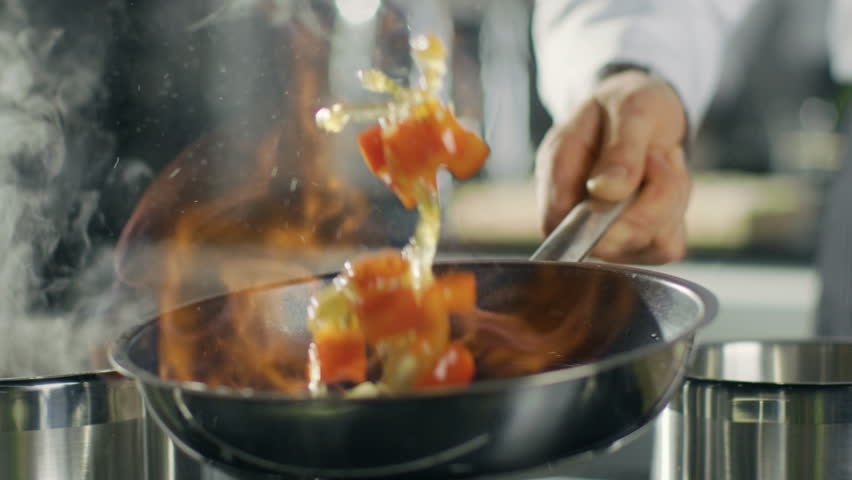 Close-up of a Chef Preparing Flambe Style Dish on a Pan. Oil and Alcohol Ignite with Open Flames.  Shot on RED EPIC-W 8K Helium Cinema Camera. | Shutterstock HD Video #28204231