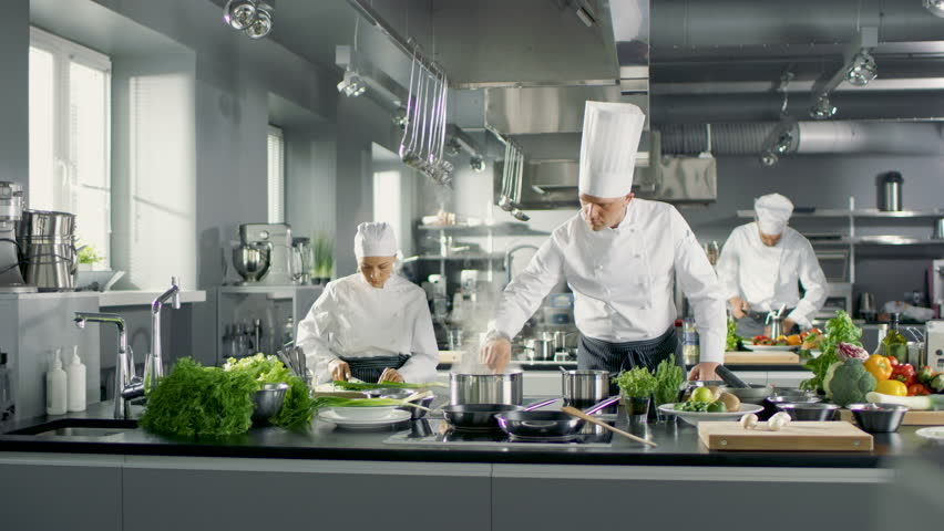 Famous Chef Works in a Big Restaurant Kitchen with His Help. Kitchen is Full of Food, Vegetables and Boiling Dishes. Shot on RED EPIC-W 8K Helium Cinema Camera.