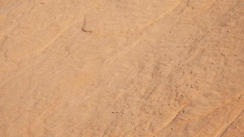 Red sand flowing down the side of dune