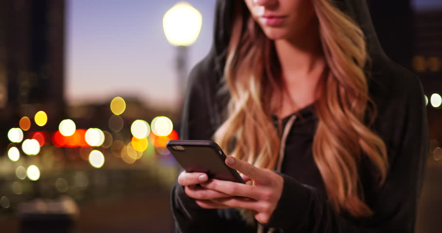 Close up of millennial girl wearing a hoodie, texting on cellphone downtown in the evening. Close-up of young Caucasian woman in a sweatshirt messaging on mobile on city street at night. 4k