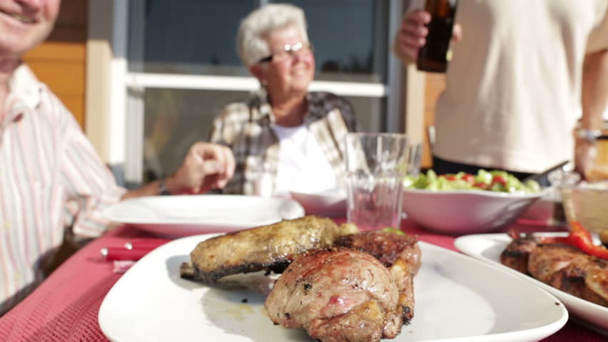 seniors at barbecue table with beer