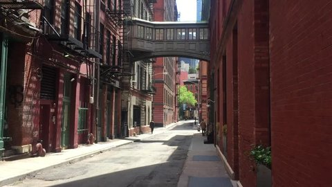 A classic daytime DX establishing shot of empty alley alleyway in New York City Manhattan in summer.  Can be used to show suspense, suspicious activity, lofts, shops, danger, lurking