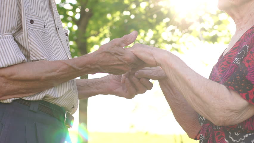 Close-up of the hands of the old grandparents in the sunny Park. Close-up grandma and grandpa holding hands in the Park at sunset.
