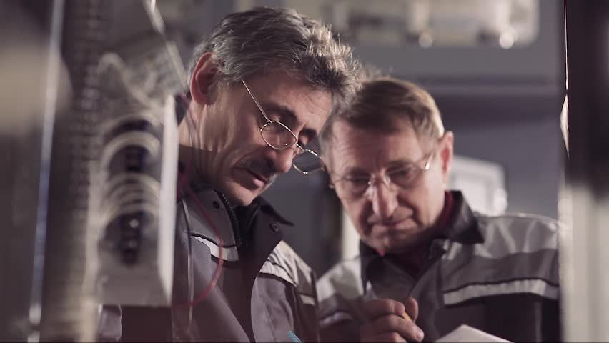 Close-up of two co-workers discussing work at a factory. | Shutterstock HD Video #28261771