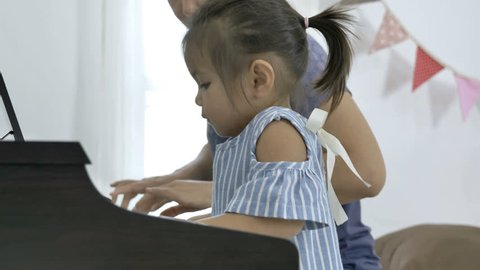 4K : Slow motion of Asian girl playing piano with her mother