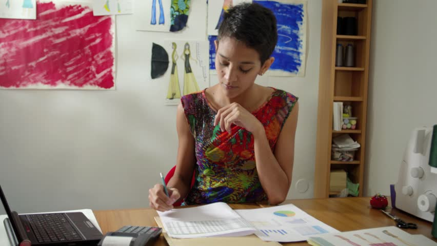 Money and financial planning, young hispanic self-employed woman checking bills and doing budget with calculator, laptop computer and papers in fashion design studio. Sequence