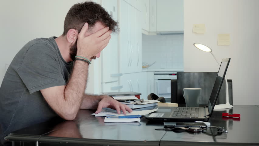 Young man overwhelmed by his bills at home.A young man at home calculates his living expenses and sums his bills and his overdue notices and falls into despair | Shutterstock HD Video #28294951