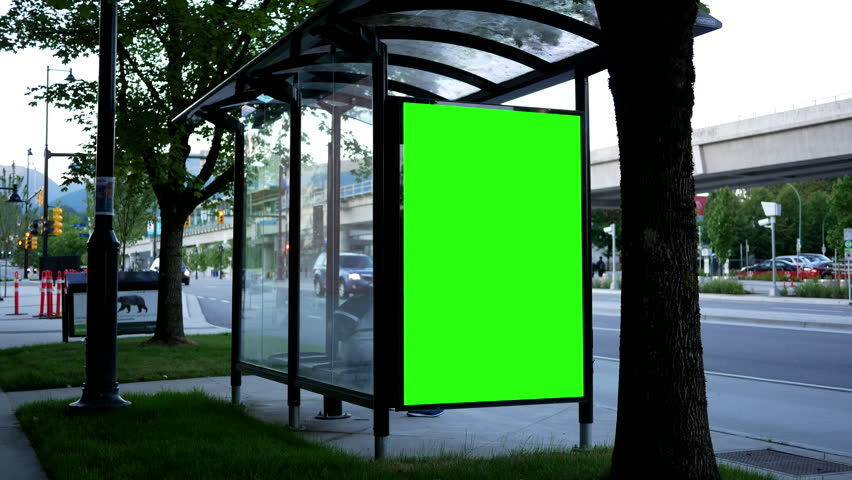 Coquitlam, BC, Canada - June 24, 2017 : Green billboard for your ad at bus station with people crossing street 4k resolution