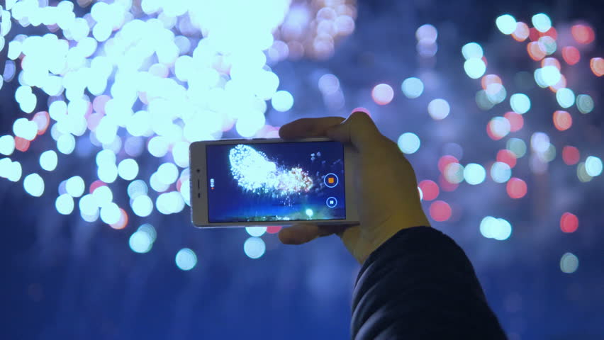 The man is holding a smartphone and recording a video of fireworks.