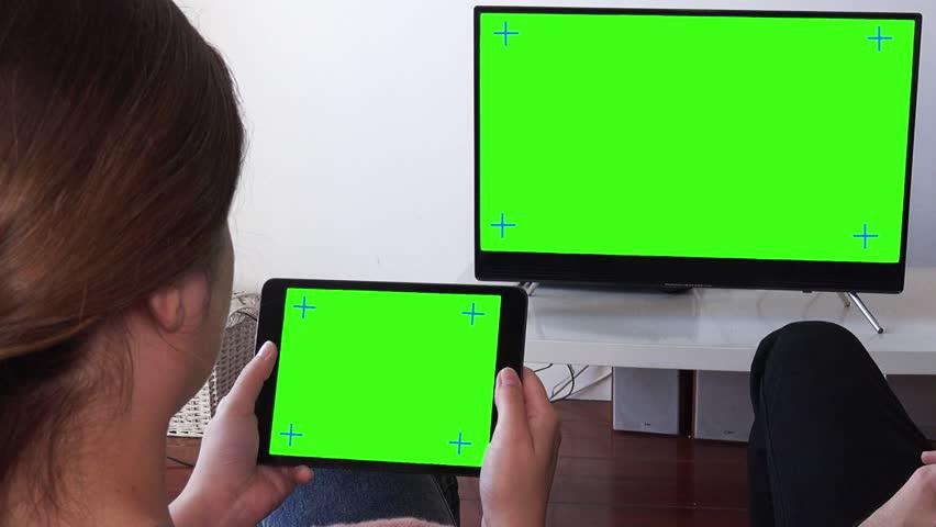 Close Up Shot of Woman Using Tablet Pan Camera To Man Watching TV Green Screen. Couple watching television green screen, close up. Shot behind models shoulders