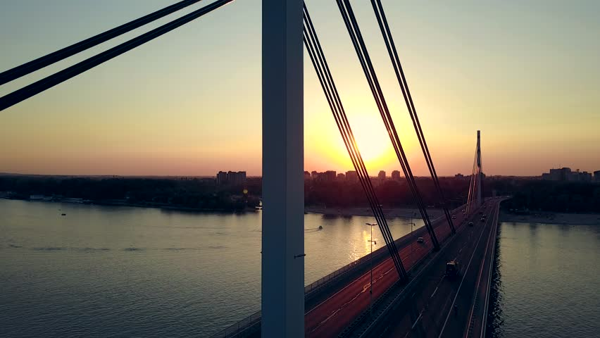 Aerial shot of the bridge over the river. Sunset drone video shot of the traffic on the bridge.