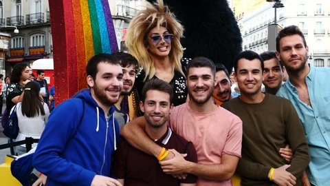 A Drag Queen in the Puerta del Sol of Madrid taking photos with the public in the celebration of Madrid World Pride, Spain. Filmed on June 29, 2017.