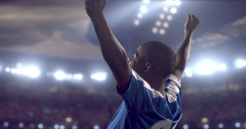 4k footage of a soccer player in celebrating a goal during a soccer game on a professional outdoor soccer stadium. Players wear unbranded uniform. Stadium and crowd are made in 3D.