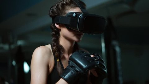 Young attractive woman boxing in VR 360 headset training for kicking in virtual reality. Slowmotion shot