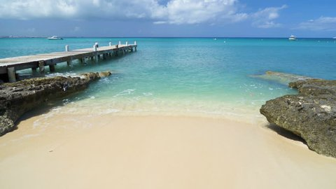 Caribbean beach background with turquoise water, pier, Grand Cayman island, and boats in the background.