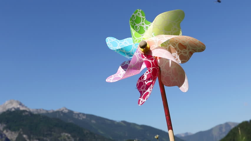 Multicolored windmill spinning in wind on blue sky and sunny day