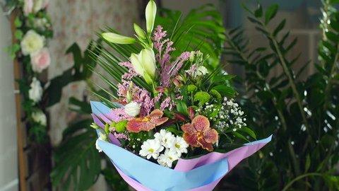 Divine beauty.Flower bouquet in the rays of light, rotation, consists of Orchid vanda, Chrysanthemum bacardi, solidago, Eustoma, Alstroemeria, Santini , gypsophila, Russus , Phoenix robbeli, Amaryllis