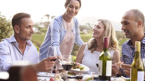 Happy smiling woman serving salad to friends and family outdoor in a sunset. Happy mature friends having dinner together. Senior men and middle aged women having fun while eating together at vineyard.
